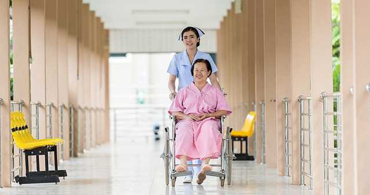 Article regarding A nurse pushes a patient in a wheelchair down a corridor