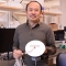 ZhongPing Lee holds a white circular Secchi disk. He stands next to cutting-edge sensing equipment in his laboratory.