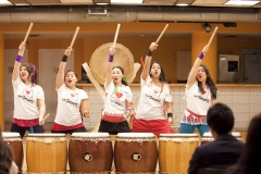 5 East and South Asian women stand in a row behind taiko drums, shouting while pointing a drumstick above their head with their right hand