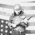 Cradling a sawed-off shotgun, a member of the Menominee Warrior Society stands in front of an upside down US flag (1975)