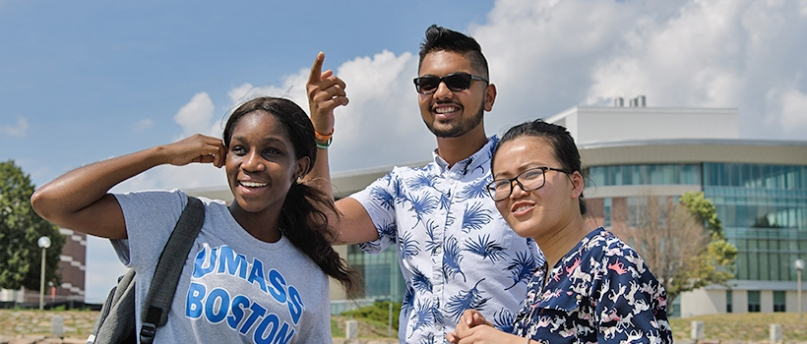 3 students, one in UMass Boston t-shirt, smiling on a sunny day with University Hall showing in  the background.