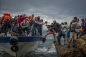 Refugees and migrants get off an overcrowded fishing boat onto the Greek island of Lesbos after crossing the Aegean Sea in October 2015. Photo credit Antonio Masiello via Zuma Press