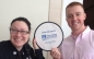 Dianne Kirkpatrick and Justin Comeau hold up a frisbee that says Catch the Alerts! UMass Boston Alert System.
