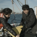 Bob Chen hoists a sensing device over the side of a boat with a student.