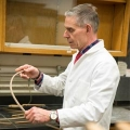 Chair and Professor of Chemistry Robert Carter shows off a bent bow.