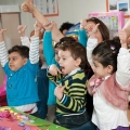 Preschool students reaching up to the sky