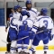 Members of the men's hockey team celebrate on the ice with a group hug