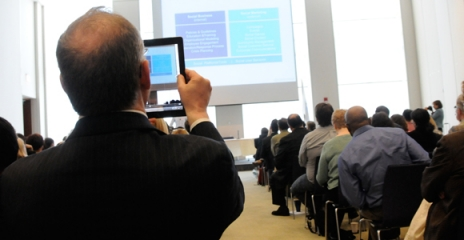 Picture of guy taking a picture of the social media presentation with his iPad.