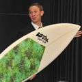Michael Emery holds one of his company's eco-friendly surfboards during the Business Launch Competition in the VDC