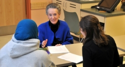 Jacqueline Fawcett meets with two nursing students.