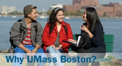 Picture of two UMass Boston students talking along the UMass Boston waterfront, with the city's skyline behind them.