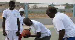 Charlie Titus plays basketball with youths who participated in summer camps in Africa  in the summer of 2010.