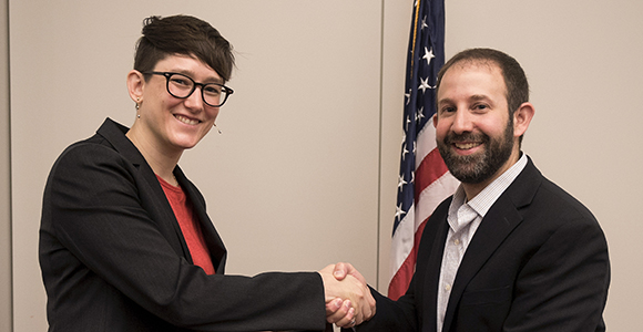 KC Kerby-Patel shakes hands with Yiftach Eisenberg, Deputy Director of DARPA's Microsystems Technology Office