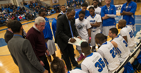 Charlie Titus goes over a play with the men's basketball team