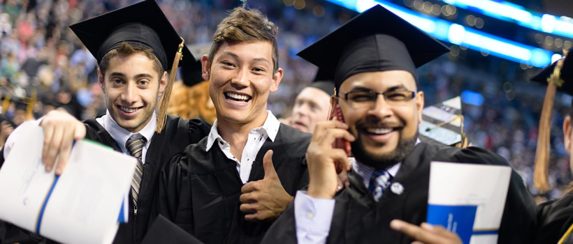 A Success Boston graduate (far right) at UMass Boston commencement at the TD Garden
