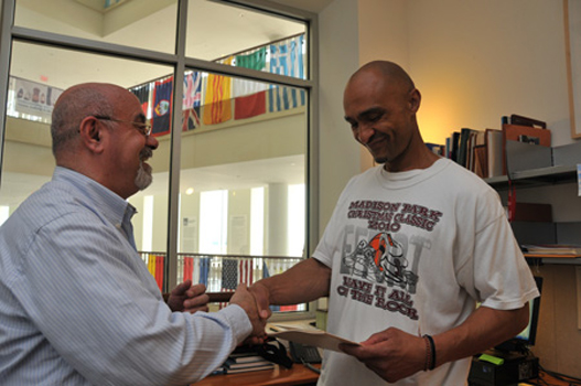 The Associate Director congratulates a student for passing the WPE.