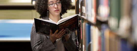 A girl looks for a book in the Healey Library on the University of Massachusetts Boston campus.