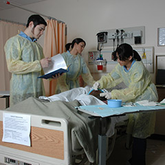 Three nursing students in scrubs. Another is in a lab coat. All are working on a pretend patient.