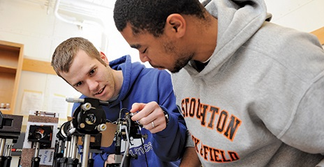 Two UMass Boston male students in a lab at work