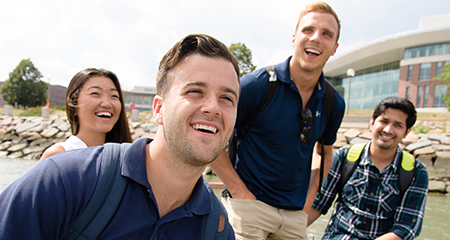 Students laugh near the water on campus.
