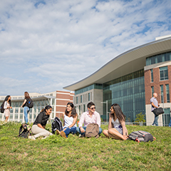 UMass Boston students sitting on the lawn in front of University Hall
