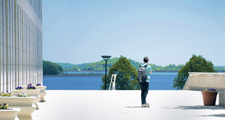 Picture of someone skateboarding by the UMass Boston campus, which overlooks the water