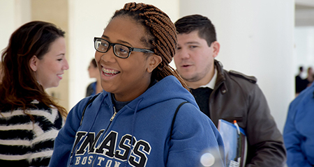A smiling student in a UMass Boston sweatshirt.