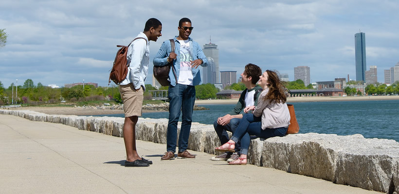 Students talking in front of the bay at UMass Boston