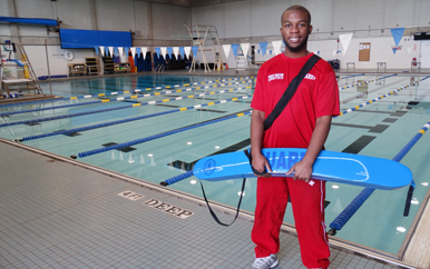 Chris the lifeguard in front of the swimming pool in the Clark Athletic Center