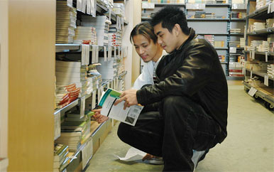 Student perusing books in UMass Boston bookstore