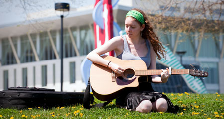 Female student playing guitar on campus