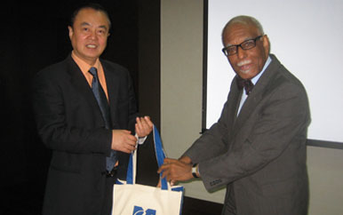 Qun Yin and Provost Winston Langley holding a UMass Boston bag.