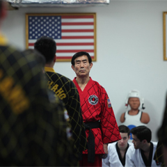 Taekwondo Grand Master Kang standing in front of his students under an American flag