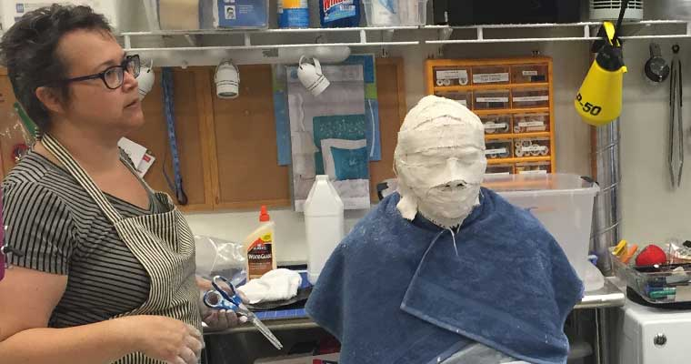 Guest artist Denise Wallace-Spriggs teaches Face Casting for Masks, Patrick McCarthy '17 listens from beneath the plaster