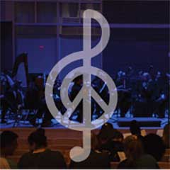 G-clef/peace symbol superimposed on the UMass Boston Chamber Orchestra playing while an audience watches