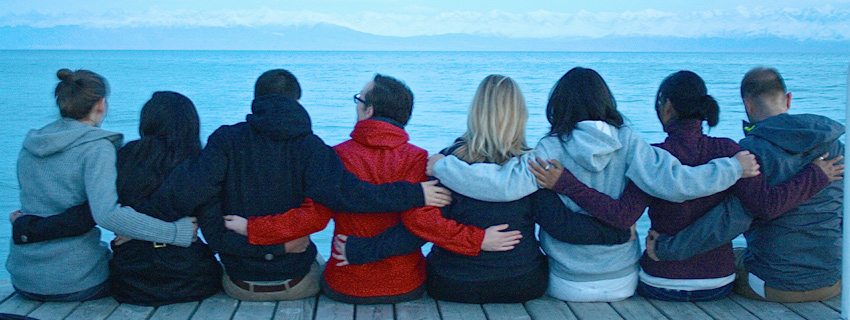 8 students arm and arm viewed from back sit on dock on trip at Lake Issy-Kul. Photo by Sheila Desai, PhD.