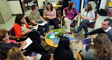 A group of students and professors sitting in a circle talking to each other.