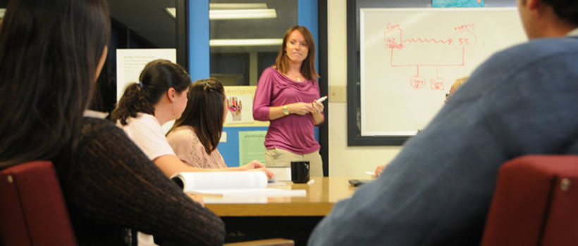 A professor in the Counseling and School Psychology program is pointing to the whiteboard during her lecture. Several students are sitting at the table listening attentively.