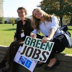 Two people holding up a sign that says Green Jobs