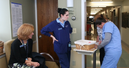 Professor Kathleen Kafel overlooking staff nurses checking in at student presentations.