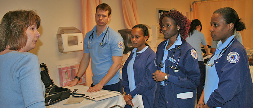 Four students and an instructor in the Center for Clinical Education and Research lab, with some equipment.