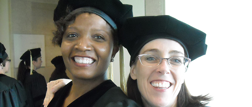 Two graduate students posing during their graduation