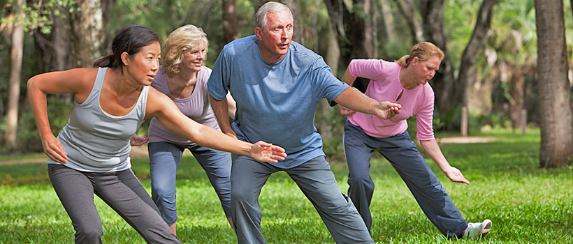 Four persons practicing Tai chi in a quiet park.