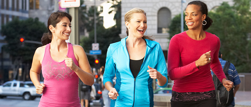 Three women jogging in the city.