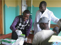 Georges Chick checking blood sugar on a patient during screening at Lari Health Center.