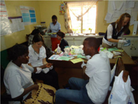 Natalie King, Jillian Phelan and Sarah Foreman conducting a health screening on patients at Kigumo Health Center.