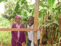 Alain, a US team member, with a gracious Kigumo community member, showing him her home and land during a community assessment.