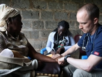 Darren taking the heart rate of a Kenyan woman.