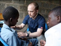 US and Kenyan nursing students collaborate to screen a young man at the community screening.