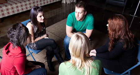 Group of students seated conducting an open discussion.